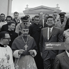 President Kennedy leaves a historic cathedral after attending Mass on St. Joseph's Day, a national holiday in Costa Rica. His next appointment for the day is a meeting with presidents from several Central American nations. Accompanying Kennedy are Costa Rican President Francisco Orlich (right) and Archbishop Carlos Umberto Rodriguez Quiros.