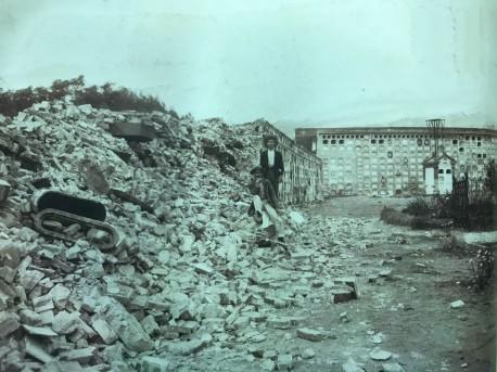 Posando con los escombros causados por el terremoto, acumulados frente a los nichos expuestos del cementerio. H.N. Rudd, 1910