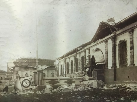 Antigua Cárcel o Cuartel de Cartago ha perdido su campanario.Al frente del reloj y entre escombros se miran algunos cuerpos en el suelo. Al fondo la casa cural de la Iglesia El Carmen. Rudd, 1910