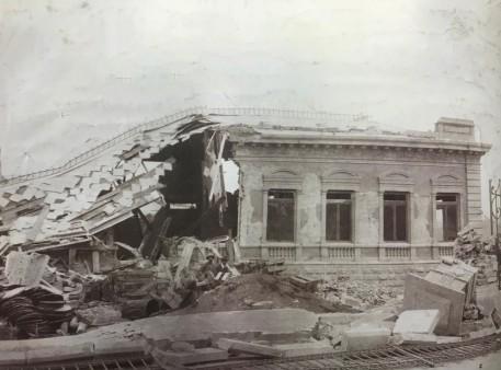 Costado Norte del Palacio Centroamericano de Juticia que fue totalmente destruido. La verja está tumbada sobre la acera. Hoy Colegio de San Luis Gonzaga. Rudd, 1910